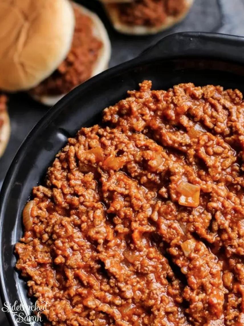 crock pot full of sloppy joes meat, with sloppy joes on bun in background