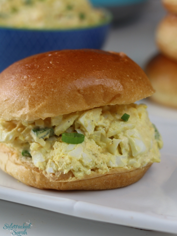 egg salad on a delicious soft bun, served on a plate