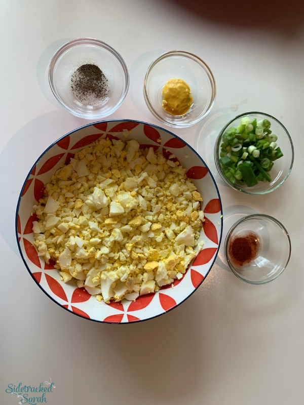 egg salad ingredients in bowls on table